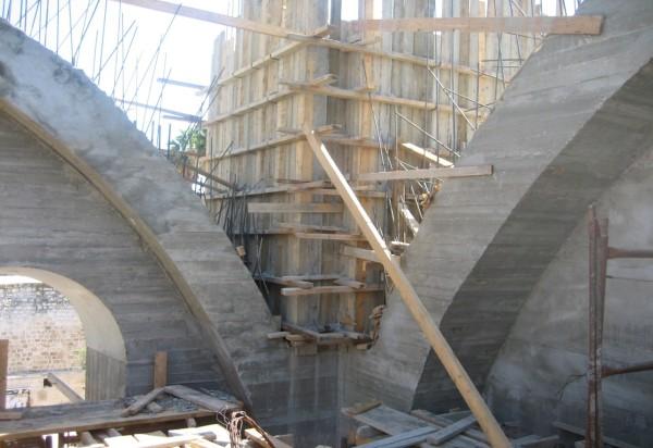 """מבט על פינת אולם בית הכנסת במהלך הבניה. שתי קשתות פנימיות מתכנסות אל עבר מגדל הפינה. בין הקשתות נבנתה מאוחר יותר """"מפרשית"""" (פנדנטיבה) שהתרוממה עד לתחתית המרפסת הפנימית."""